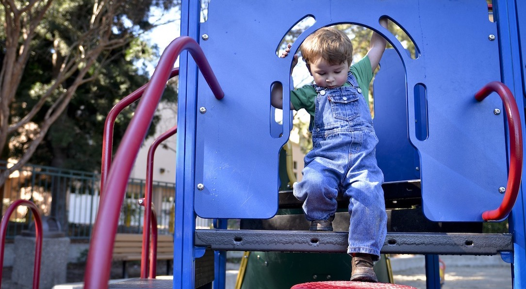 Young boy stepping down from tall blue playground equipment platform onto a red step